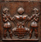An 18th century carved oak armorial panel Worked with an heraldic shield flanked with mace bearers.