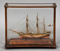 A small scale model of the three masted vessel Manila Housed in mahogany framed bevel glazed display