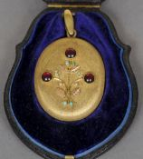 A 19th century garnet and turquoise set two tone yellow metal pendant locket Of oval form and worked