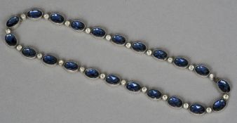 A 19th century blue and clear paste set white metal backed necklace Set with alternate stones.  40