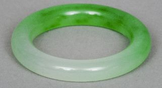A Chinese carved jade type bangle Light green.  8.5 cm diameter. CONDITION REPORTS: Generally in