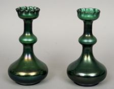 A pair of green iridescent Art glass vases Each with a crimped neck rim above a knopped stem with