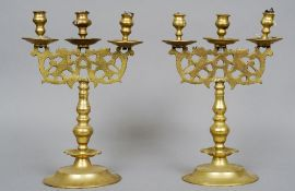 A pair of French brass three branch candelabra Each with pierced cast panels with mythical