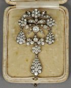 A 19th century paste set white metal backed brooch Modelled as a floral spray with triple pendant