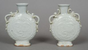 A pair of Chinese Ming Dynasty moon flask celadon vases Each with twin scrolling handles decorated