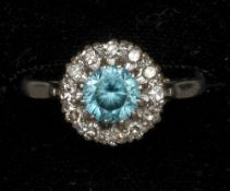 An 18 ct white gold and platinum diamond and aquamarine target set ring The central round facet