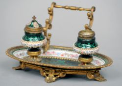 A 19th century gilt metal mounted Bilston enamel desk stand The oval tray fitted with two ink stands