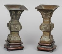 A pair of Chinese bronze gu vases Each typically worked and standing on a carved wood base.  18