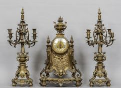 A 19th century Gothic Revival gilt brass cased clock garniture The clock with floral urn surmounts