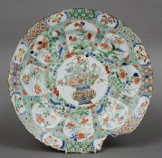 An 18th century Chinese famille verte porcelain charger Centred with a basket issuing flowers within
