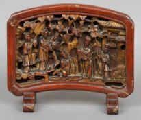 A Chinese carved wood and red lacquered table screen Worked with various figures in a garden