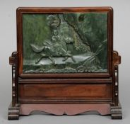 A Chinese hardwood framed carved jade table screen Decorated with Buddha astride a horse, mounted on