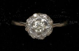 An 18 ct gold diamond target set ring The central claw set stone approximately 0.25 carat, flanked