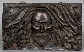 A 17th century style carved oak panel Centred with the bust of a bearded gentleman flanked by oak
