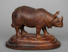 A carved rosewood model of a rhinoceros Naturalistically modelled on all fours, standing on a