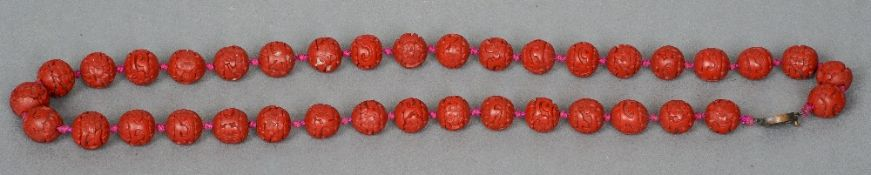 A Chinese cinnabar lacquer carved bead necklace Each with scrolling foliate designs.  66 cm long.
