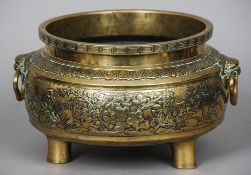 A large Chinese bronze censer Of squat form, with Greek key border above twin mask headed loop