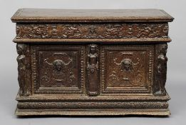A 17th century and later carved oak coffer The rectangular hinged lid above a putto carved frieze