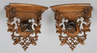 A pair of early 20th century Black Forest carved wall brackets Each of scrolling floral form centred