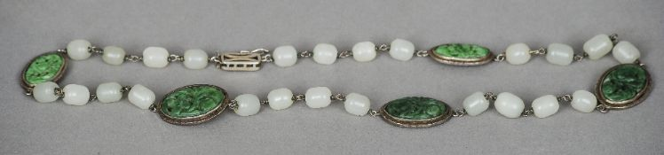 A Chinese carved spinach jade and mutton fat jade necklace The carved spinach jade roundels