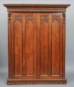 A Victorian carved oak Gothic Revival wardrobe,