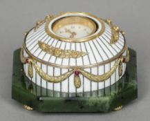 An unmarked gold and ruby set white enamel decorated desk clock Of domed form, standing on a spinach