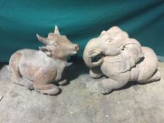 Two Indian terracotta animalier sculptures One an elephant, the other a cow, each in recumbent