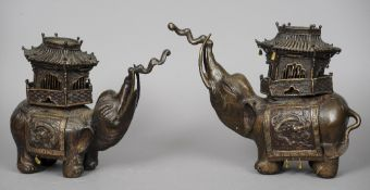 A pair of Chinese patinated bronze elephant form censers Each typically modelled with a pagoda top.