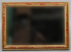 A chinoiserie lacquered wall glass The bevelled plate within a cushion moulded frame with iron red