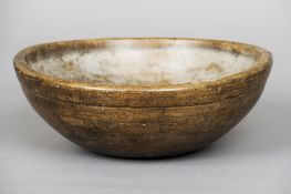A 19th century turned sycamore dairy bowl Of typical form, the exterior with banded detail.  41 cm