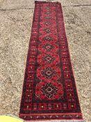 A Caucasian wool runner The wine red field enclosing ten cruciform guls within rosette guard stripes