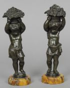 A pair of patinated bronze models of putti Each carrying a basket, one with fruiting vines, the