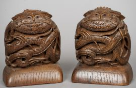 A pair Eastern carved hardwood bookends Each worked with a bearded mythical beast.  18 cm high.  (2)