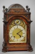 A 19th century walnut bracket clock The bronze finial mounted domed case enclosing the silvered dial