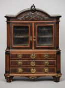 A 19th century Dutch miniature cabinet The carved arched top above twin glazed doors enclosing