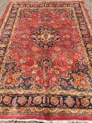 A Meshed wool carpet The wine red field enclosing a central medallion with pendant palmettes