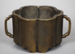 A Chinese bronze twin handled censer Of lobed form, archaic three character seal mark to base. 17 cm