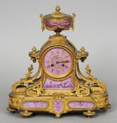A 19th century porcelain mounted ormolu mantel clock The urn form finial above the enamel beaded