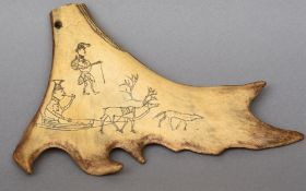 A small piece of scrimshawed elk or caribou antler Decorated with an elk towing a sled, figures