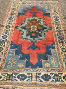 A Caucasian wool rug The wine red field enclosing a central medallion with stylised pendant