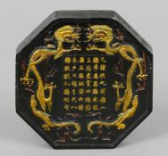 A Chinese ink block Of octagonal form, one side decorated with two dragons centred with text, the