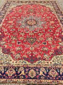 An Isfahan wool carpet The wine red field enclosing a central medallion with pendant palmettes