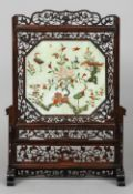 A Chinese carved soapstone and hardstone pierced hardwood framed table screen The central panel