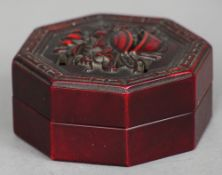 A Chinese carved red stone seal Housed in a carved and pierced octagonal hardstone case.  7 cm wide.