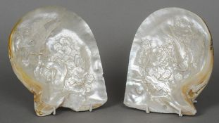A pair of carved mother-of-pearl shells Each decorated with a bird amongst foliage.  The largest