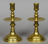 A pair of brass Heemskirk candlesticks Of typical form, with central drip-pan, standing on a domed