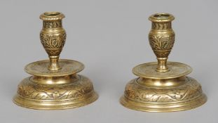 A pair of 19th century bronze candlesticks With allover foliate scroll and flowerhead decoration.