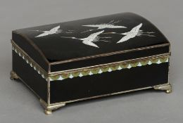 A Japanese cloisonne box The hinged domed cover decorated with cranes on a black ground, the