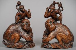 A pair of Chinese carved wooden monkey groups Each worked as a crouching monkey with another