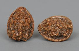 A pair of Chinese canton carved nuts Each profusely worked with figures.  4.5 cm high.  (2)